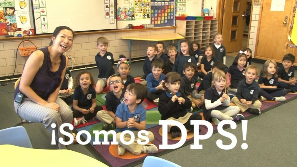 "Kindergarten students and teacher smile at the camera. Text ""¡Somos DPS!"" is visible at the bottom of the image."