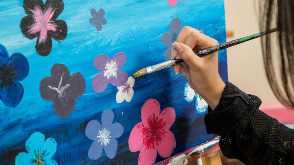 Student painting flowers on a canvas