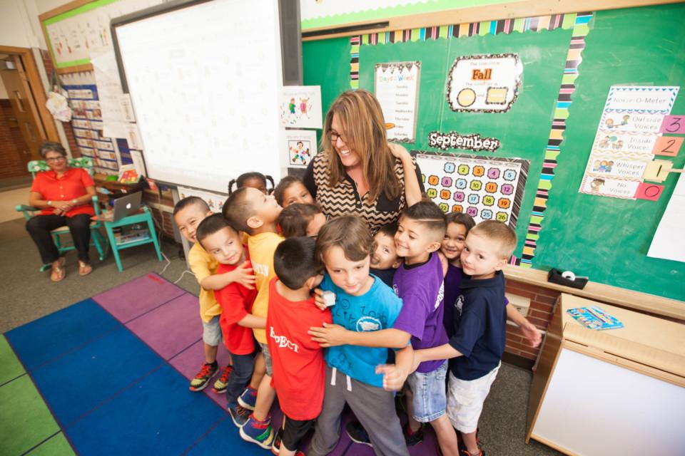 Students hugging their teacher