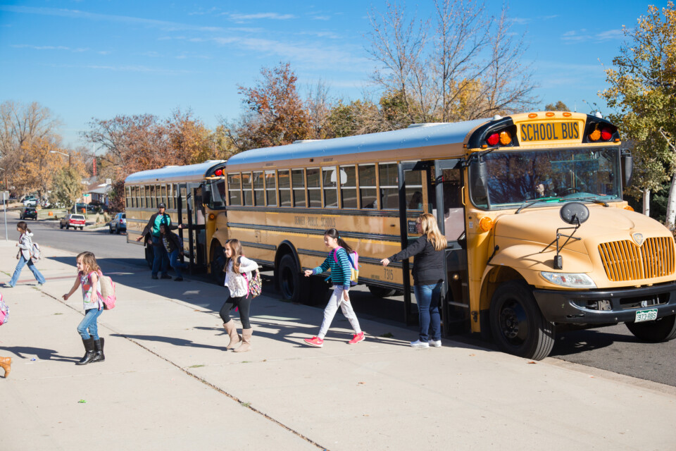 Children walk off of a Denver Public Schools school bus as they head into class