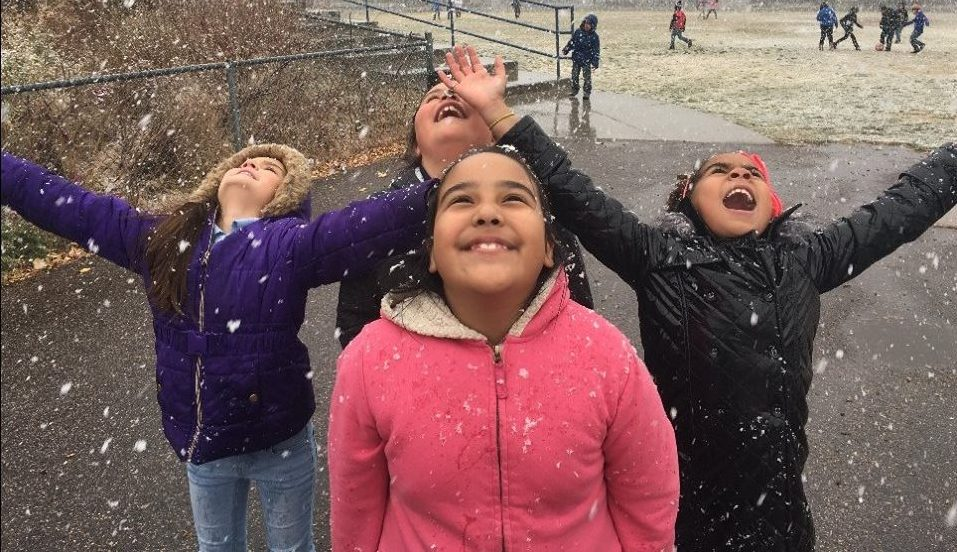 Students smile while looking to sky as snowflakes fall