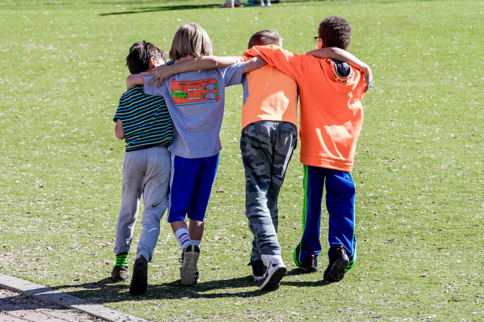 Four elementary students walk arm-in-arm on a field