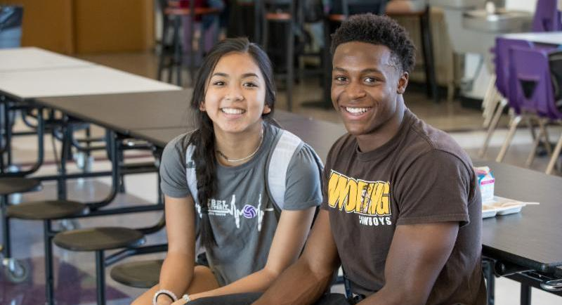 Two high school students sitting in a cafeteria.