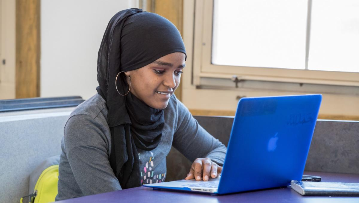 Student smiling while using a laptop