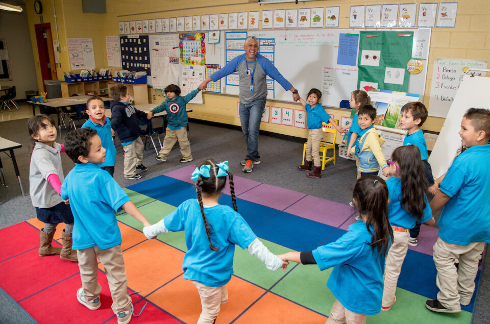 Elementary students and teacher hold hands and dance around in a circle in a colorful classroom.