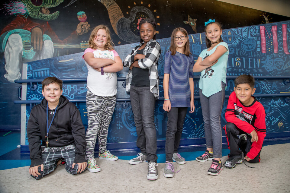 Six DPS students from Isabella Bird Community School pose in front of a colorful mural.