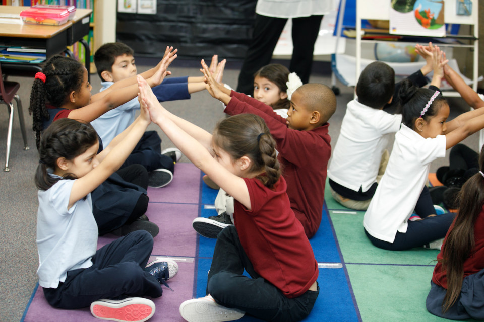Young students with their arms up participating in an activity