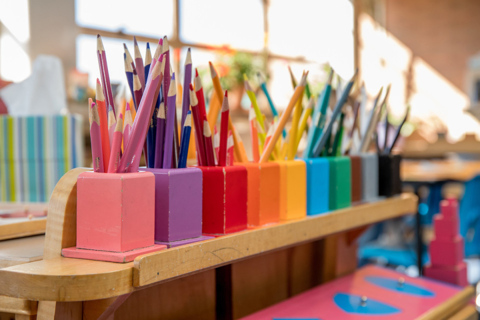 Rainbow boxes in a row filled with colored pencils in a sunny classroom
