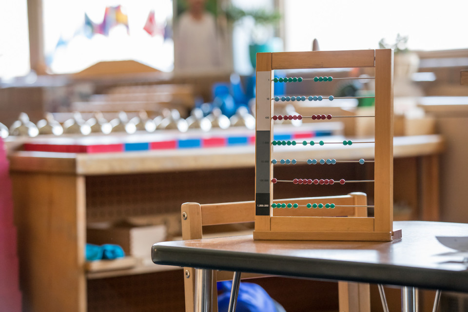 A bright sunny classroom with bookshelves and an abacus.
