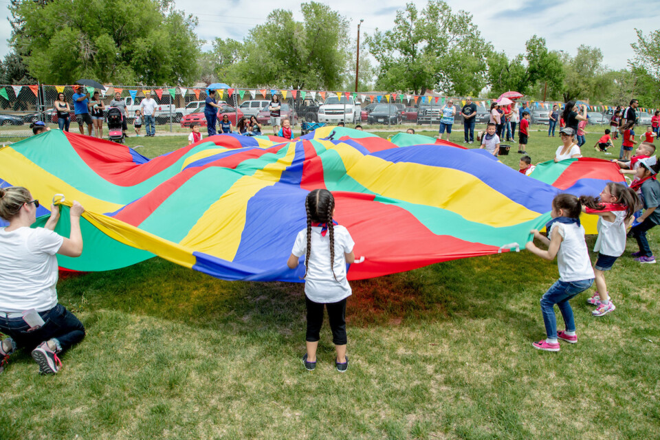Students play with parachute outside on a field