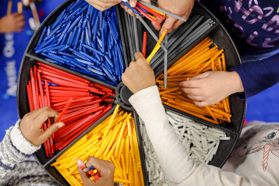 overhead angle of a box of different colored pencils, with students' hands reaching in and exchanging