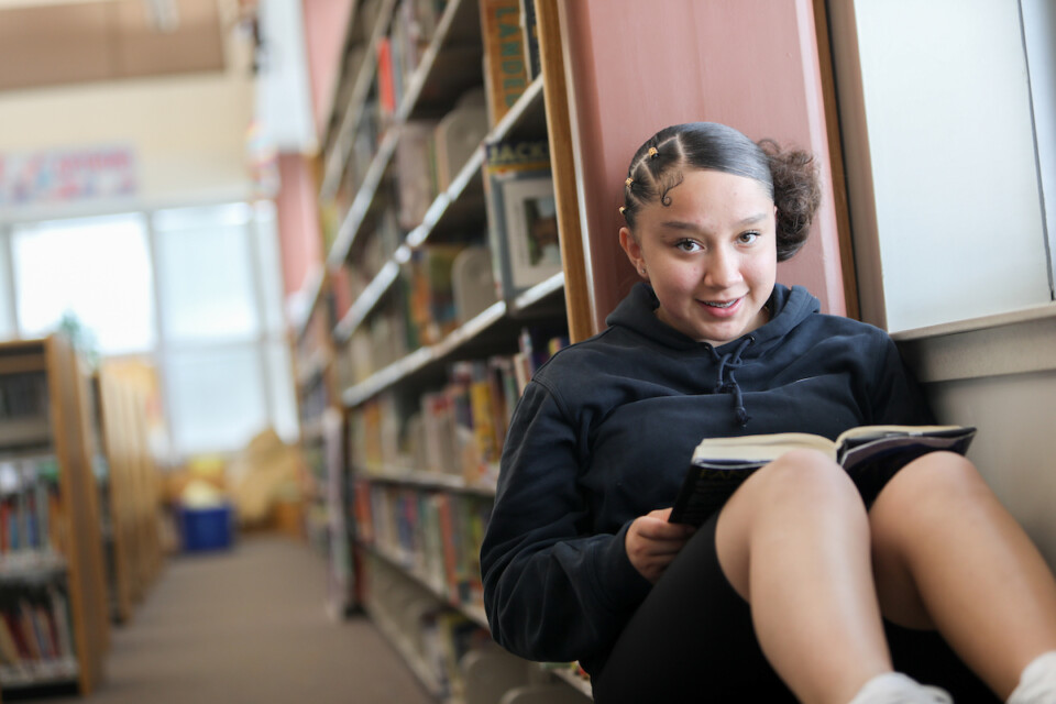 Student reads in the library at Farrell B. Howell