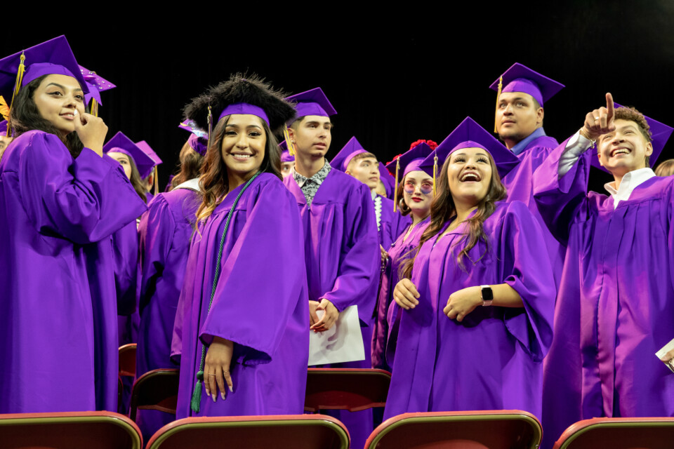Students smile in purple caps and gowns at North High School graduation
