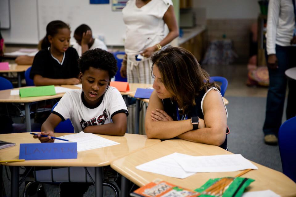 Superintendent Cordova and Hallett Academy student talk in a classroom.