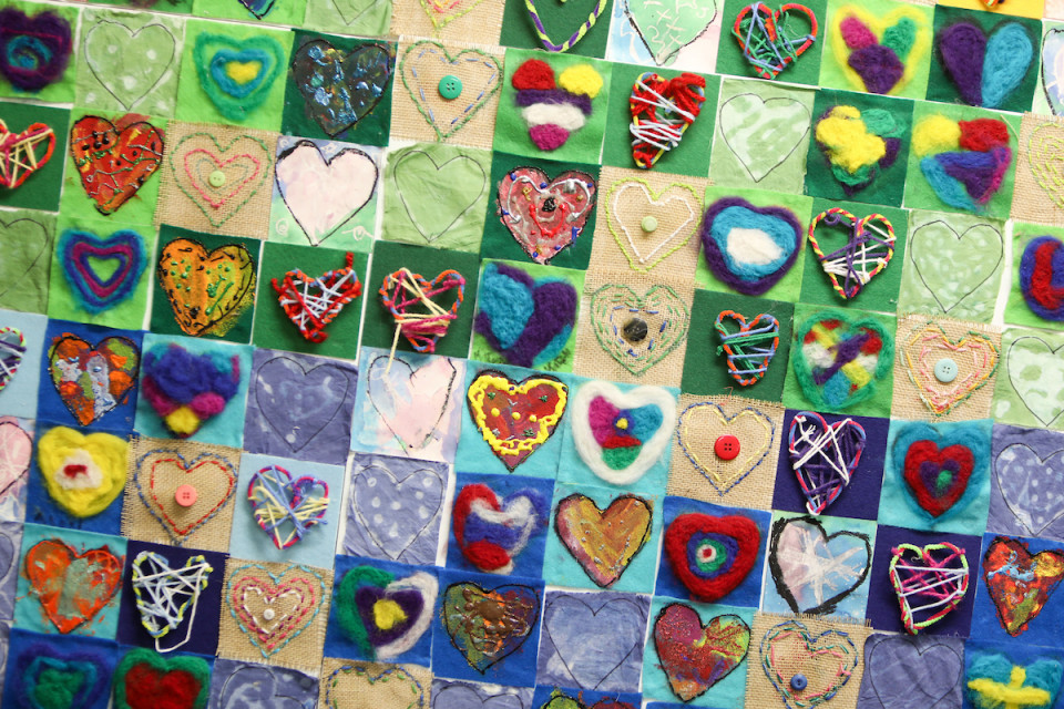 Handmade mosaic or quilt with colorful heart shapes from Southmoor Elementary