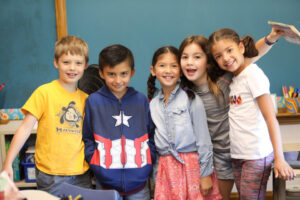 five elementary students smile in a group for the camera at Steck Elementary