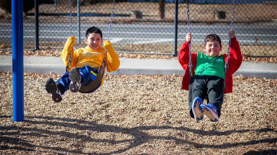 Two students smiling while playing on swings