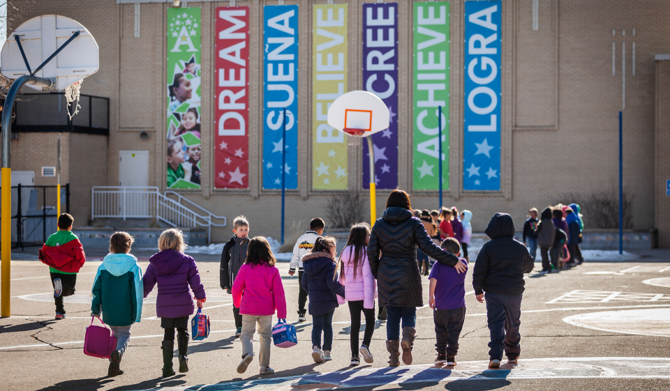 Students at Ashley Elemtary walk toward their school with an adult. Banners on the school read: Dream, Suena, Believe, Cree, Achieve, Logra.