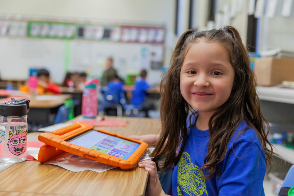 Smiling elementary student sits at her desk with a computer