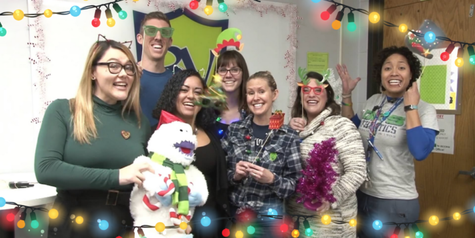 A group of educators pose for the camera with holiday-themed props