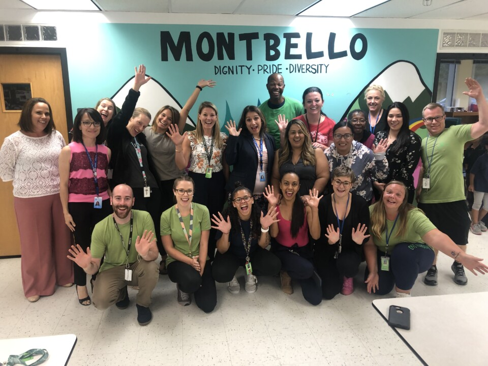 Educators pose for a photo, smiling and raising their hands against a Montbello backdrop