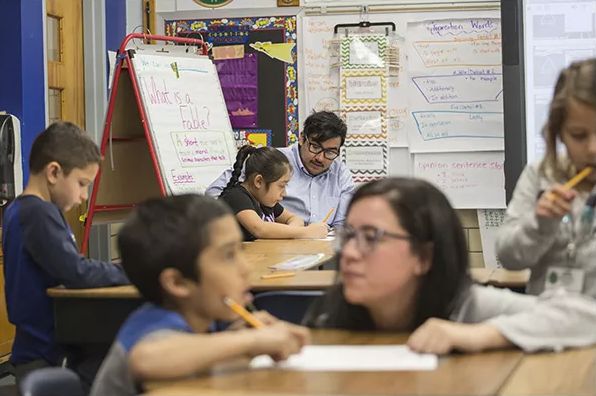 Nineteen-year-old Angel Magana, seated in the rear of the classroom, is in a Denver teacher-residency program that allows him to work as a paid paraprofessional while working toward his teaching degree. —Nathan W. Armes for Education Week
