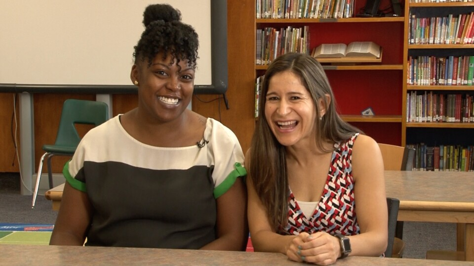 Two Valverde Elementary teachers smile for a photo while seated in a library