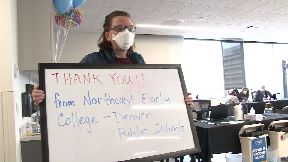 "DPS staff holding whiteboard that reads ""Thank you! from Northeast Early College, Denver Public Schools!"""