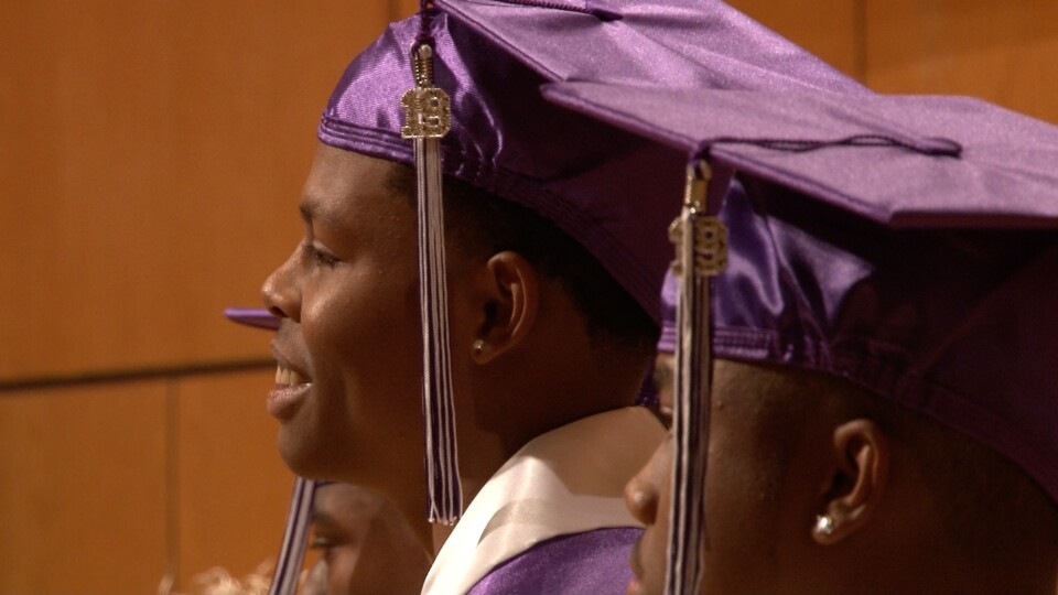 Student wearing a graduation cap, gown and tassel smiles while looking off camera