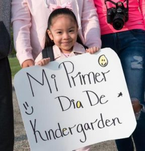 "A student from Escalante-Biggs Academy holding a sign saying, ""My first day of Kindergarten."""