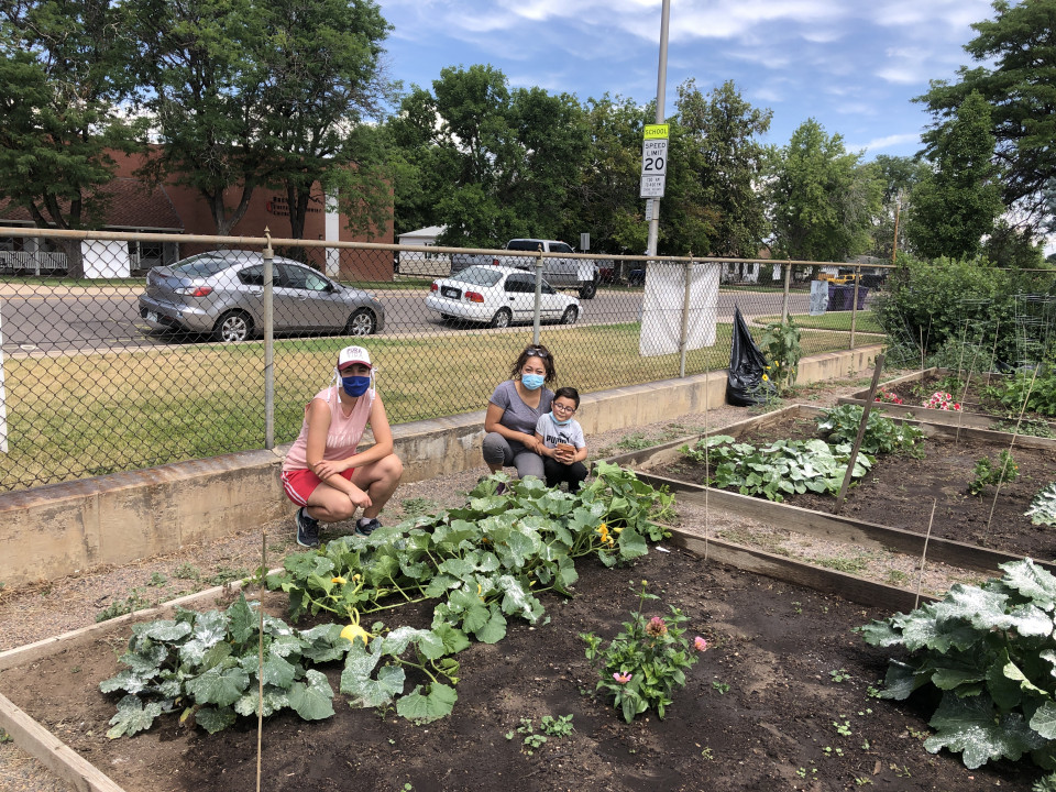 Two community members and a young child pose next to a thriving vegetable garden