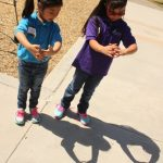 Students using their hands to view the solar eclipse on the first day of school at Newlon.