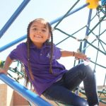 A student plays on the jungle gym at Newlon Elementary on the first day of school.