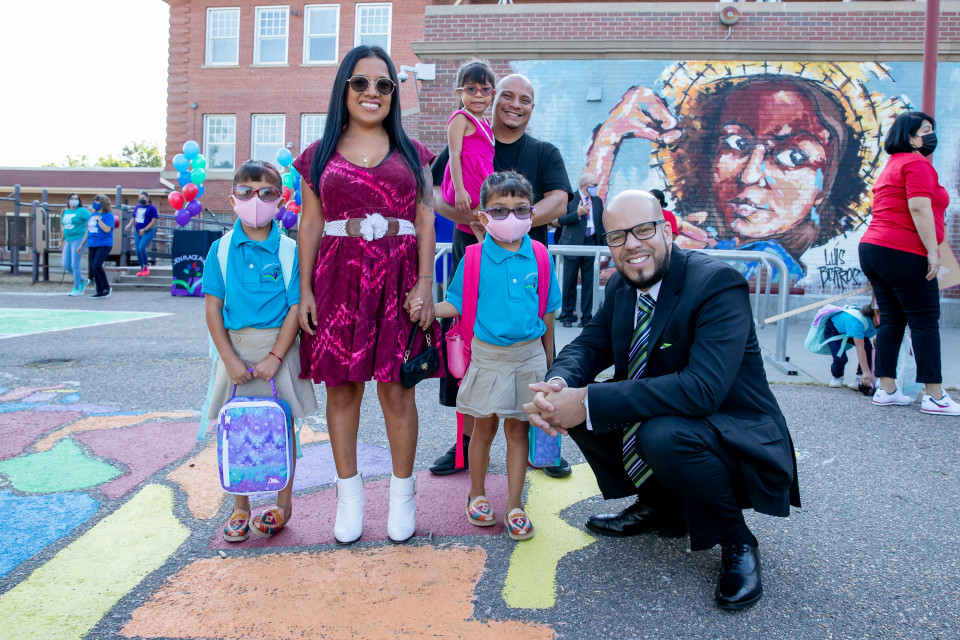 Dr. Alex Marrero outside of a school with a family