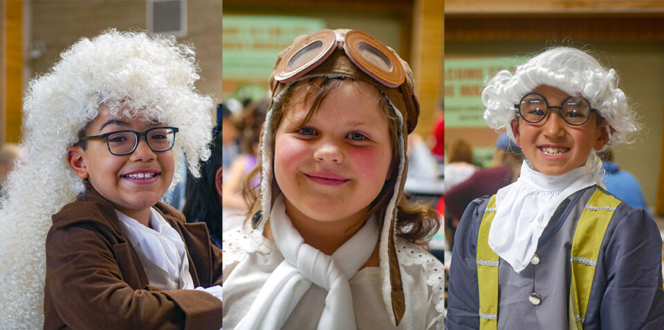 Three elementary school students wear costumes of historical figures.
