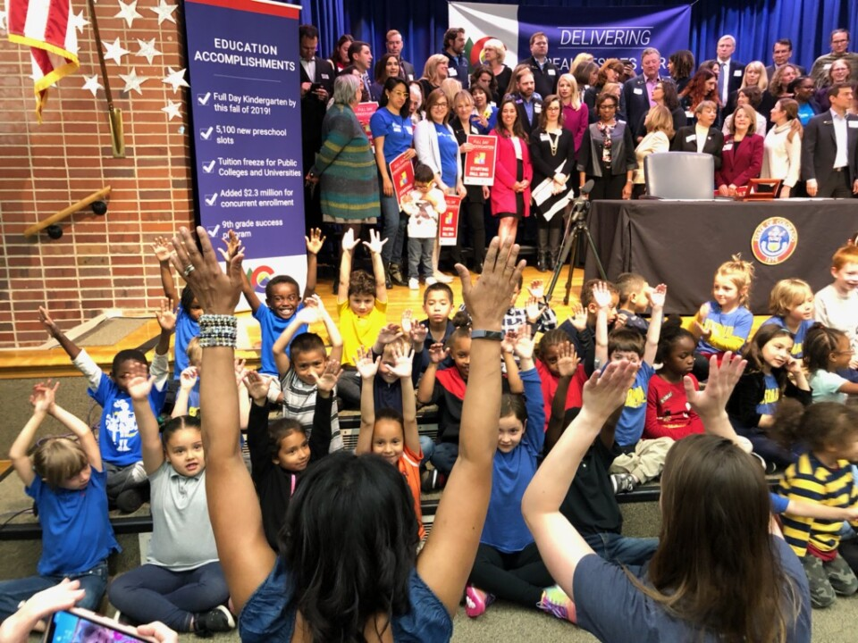 A happy group of kindergarten students sings a song with their hands in the air in anticipation of the Governor signing the free kindergarten bill into law at Stedman Elementary.