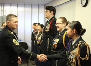 Students in DPS JROTC programs smile while shaking hands during an awards ceremony