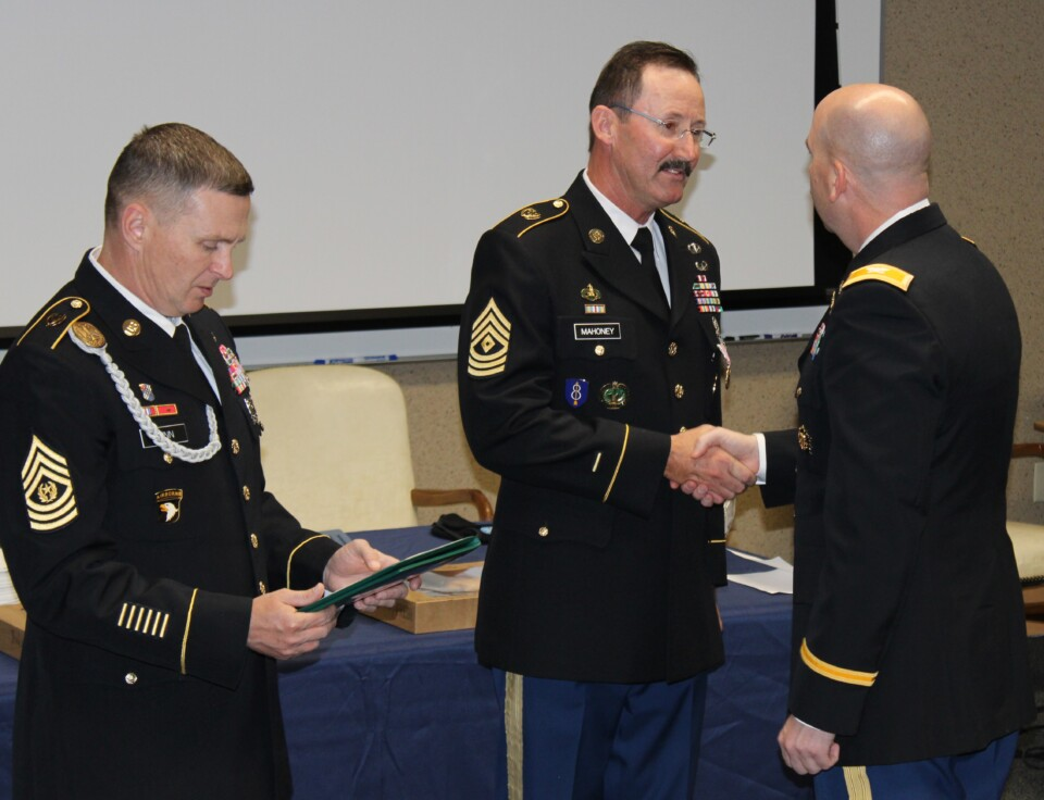 Two DPS JROTC Instructors shake hands as they receive awards