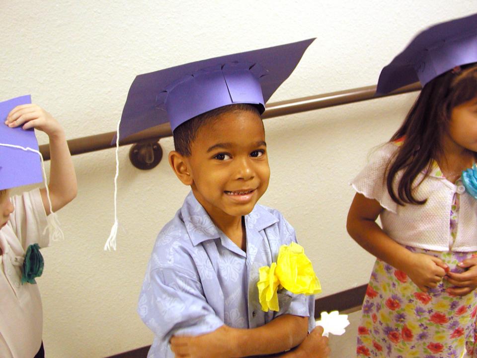Young kindergarten student smiles wearing a graduation cap