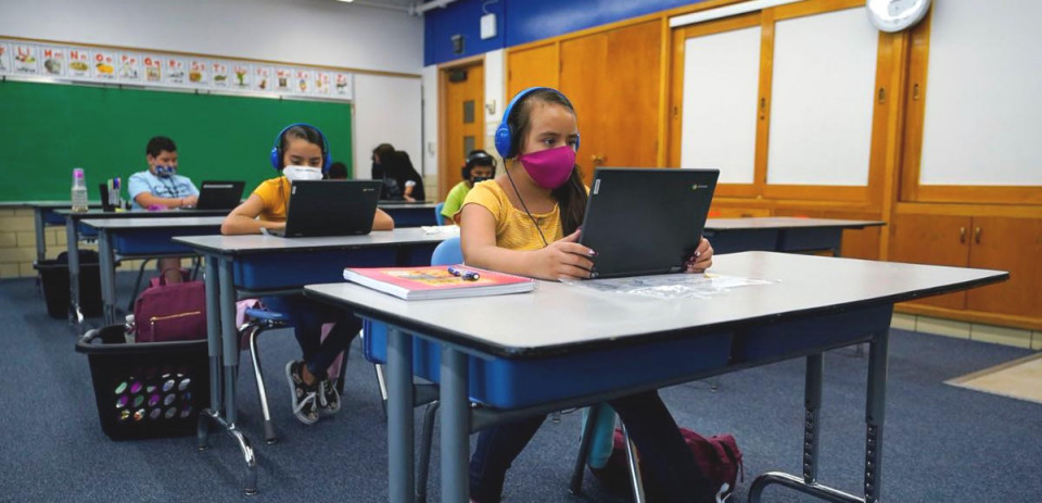 Students with masks on laptops in a classroom