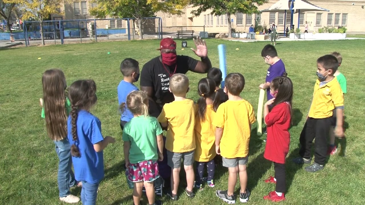 PE coach and students - all masked - gather in a circle outdoors