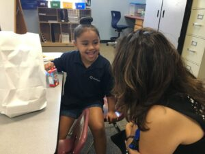 A student smiles while talking with Superintendent Susana Cordova during lunch