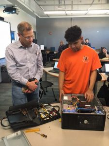 A West Campus student shows Supt. Tom Boasberg how to reassemble hardware.