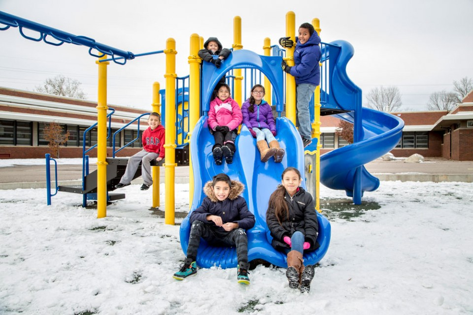 Students sit on a play structure as snow lies on the ground around them
