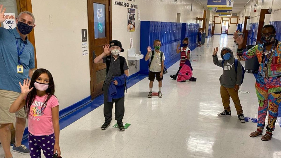 Students wearing masks and waving in a school hallway