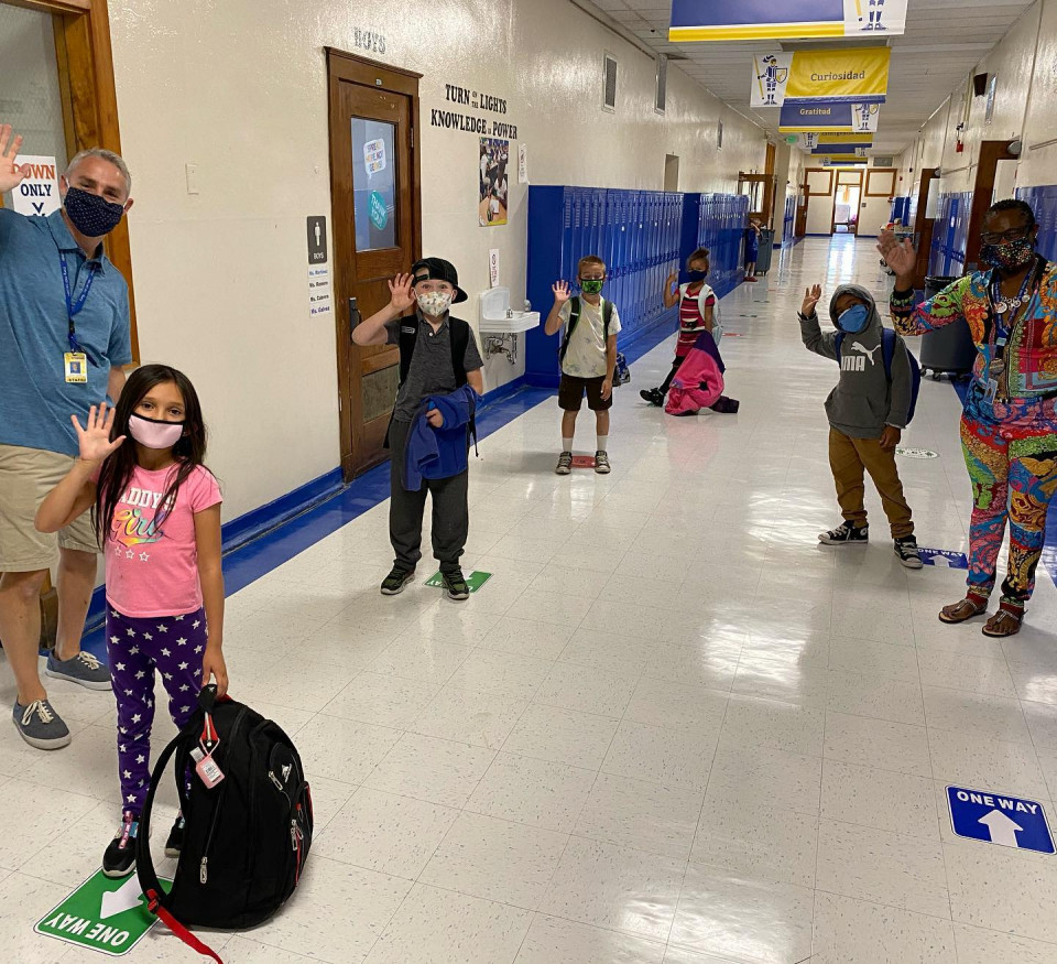 Students posing in the hallway with masks