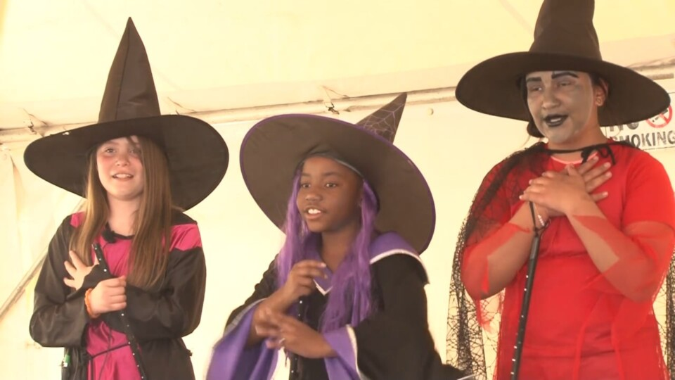 Three students - dressed as witches - perform a scene from a work by William Shakespeare