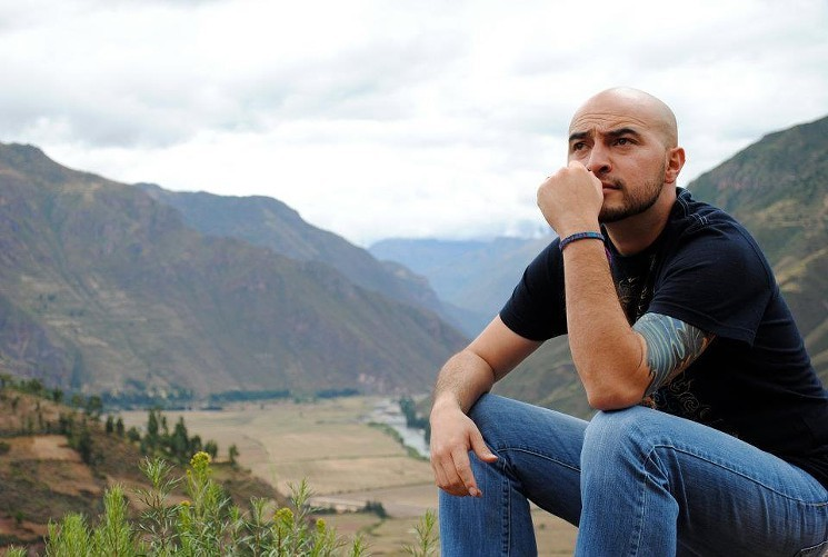 Bobby Le Febre poses for a photo, looking off into the distance against a backdrop of mountains.