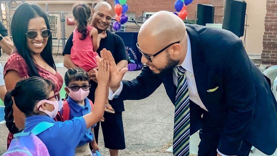Superintendent Dr. Alex Marrero high-fives a student