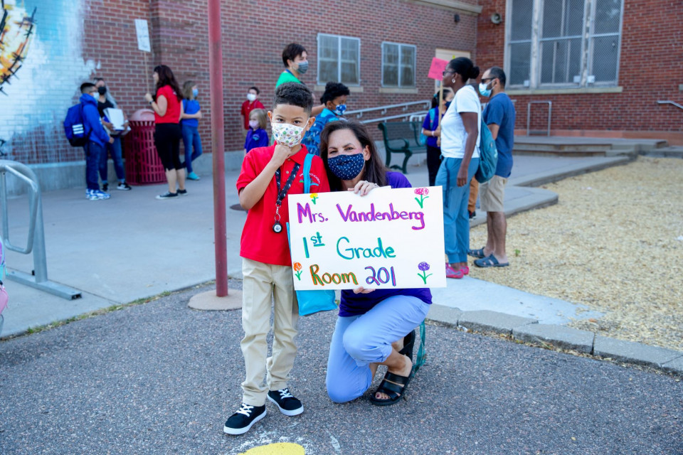 A teacher - holding a sign with her name, 1st grade, and room number - poses for a photo outside with a child while both wear masks.